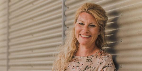 Louise Brinking i blomstret bluse op af væg